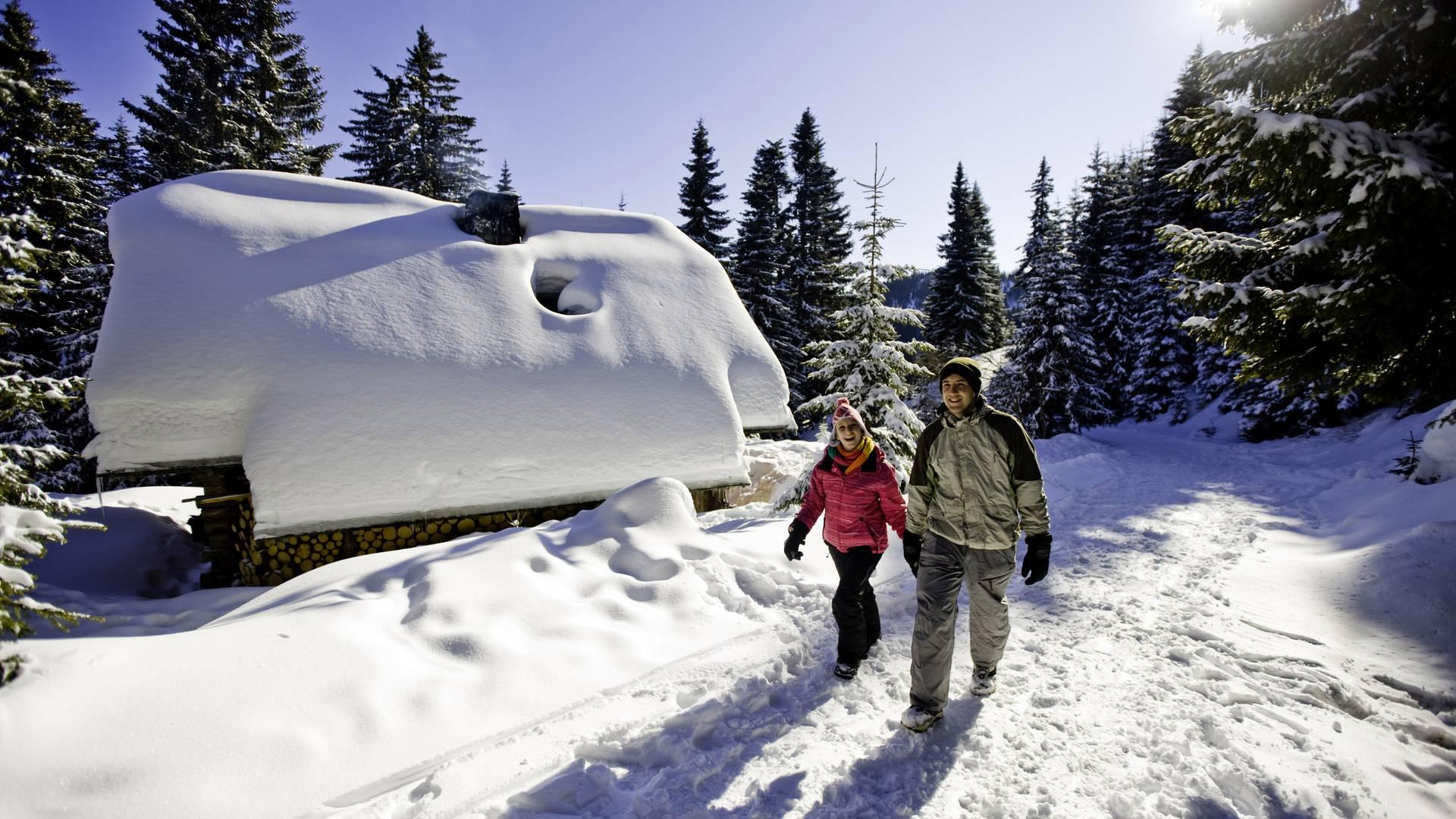 Winterwandern vor der tiefverschneiten Hütte